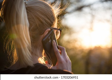 Backlit rear view of young woman talking on cell phone outdoors in park at sunset. Girl holding mobile phone, using digital device, looking at setting sun. Copyspace.