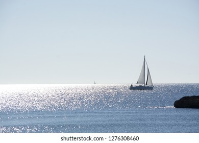 Backlit sailboat on bright and sunny sea with horizon on a winter day in Mallorca, Spain