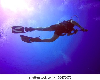 A backlit scuba diver silhouette. View of the scuba diver gear, fins and bubbles underwater in the deep blue sea of Limassol, Cyprus against the sunlight.