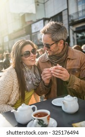 Backlit shoot. Trendy couple having fun and sitting at a terrace in the city center. The woman is wearing a woolen coat,The grey hair man has  a leather coat A shopping bag is on the bar table