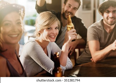 Backlit shot with flare. Friends having a drinks on a sunny evening in a bar, They are sitting with beers. They are wearing casual clothes. Focus on a gorgeous blonde girl touching her bottle.