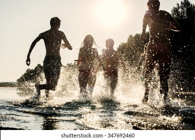 Backlit shot of teenagers running with their feet in the water at the beach during a sunny afternoon during summer break. They are having fun, playing and splashing water around them