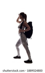 Backlit silhouette of a female model posing as a hiker on a white background wearing a backpack.  The image has copy space and isolated for composite cut outs to add backgrounds