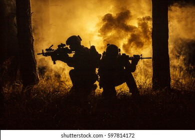 Backlit silhouette of special forces marine operators in forest on fire explosion background. Battle, bombs exploding, they fighting no matter what