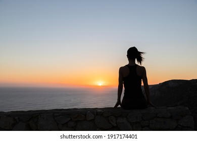 Backlit silhouette of a woman watching the sunrise over the sea