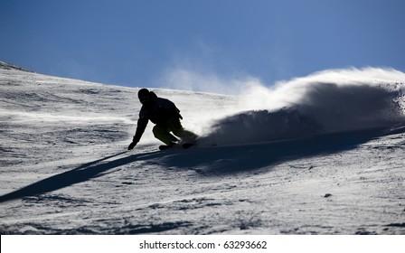 Backlit skier splashing snow powder while turning and skiing fast