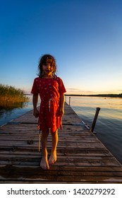 Backlit summer night portrait of a young caucasian girl in red dress on a jetty with water and blue sky.