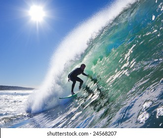 Backlit Surfer on Big Wave in the Tube on a Sunny Blue Sky Day