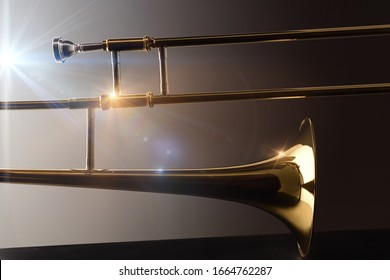 Backlit trombone on black base trombone concert concept with lights and dark background. Side view. Horizontal composition.