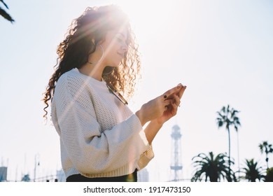 Backlit view of millennial blogger using cellphone technology for creating travel publication and share to social media during network browsing in city, curly hipster girl reading received message