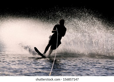Backlit waterskier and spray