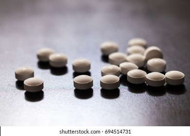 Backlit white pills - Opioid and prescription medication addiction epidemic or crisis - concept