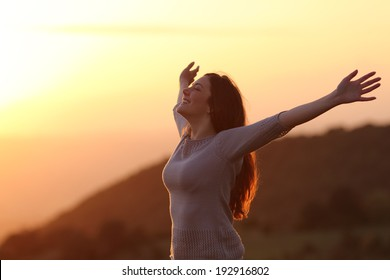 Backlit of  a woman at sunset breathing fresh air raising arms