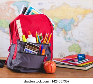 Backpack with an assortment of school supplies on a wooden table with a world map in background