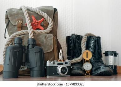 A backpack, binoculars, compass, pocket watch, rope and photo camera on a floor on a white wall background . Travel or adventure background.