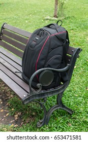 Backpack Black color put on the Green chair In garden.
