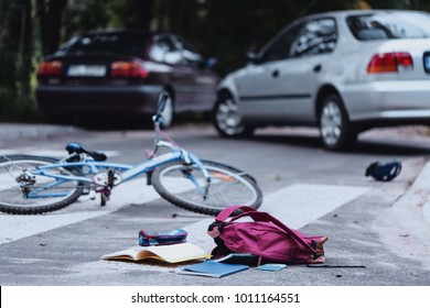 Backpack and broken child's bike on the street. Child hit by a car concept