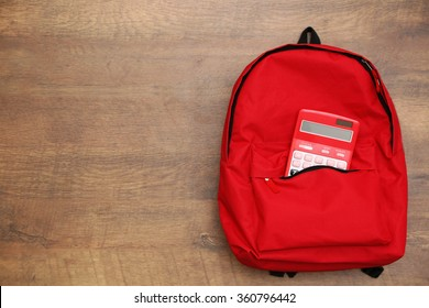 Backpack and calculator on wooden background