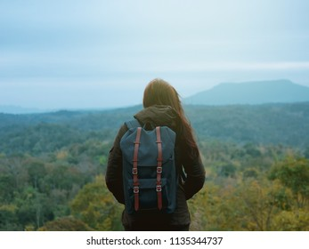 backpack and camping concept from backside of long hair woman in warm cloth with her bag travel, relax, happy  and see to forest and mountain in morning after sunrise