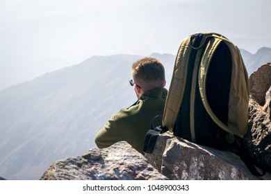 Backpack climber resting near the Jebel Toubkal peak, Atlas mountains, Morocco.