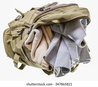 The backpack of color khaki, lies opened and in it two warm sweaters are visible. It is isolated on white, a horizontal shot