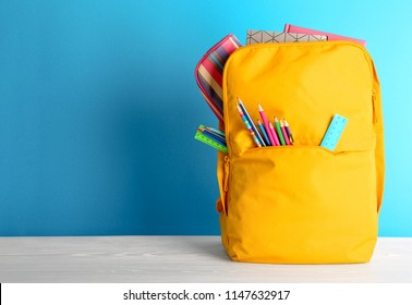 Backpack with different colorful stationery on table. Back to school