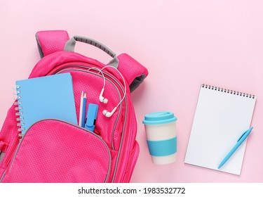 Backpack filled with school supplies and reusable eco cup on pink background. Top view, mockup blank
