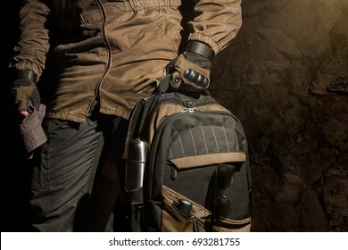 Backpack and gear composition.Man in storm jacket and tactical military gloves holding a backpack with travel gear on stone wall background.
