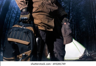 Backpack and gear woods composition. Man in storm jacket and tactical military gloves holding a backpack with travel gear on lightened tent in dark woods background.