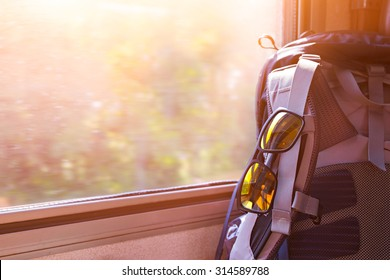 Backpack with glasses on seat in moving train. Stock image for traveling concept