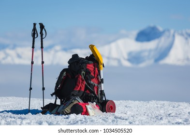 Backpack and hiking poles of a hiker in the snow. Winter adventure concept.