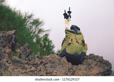 backpack with hiking poles on volcanic rock in Etna Park, Sicily