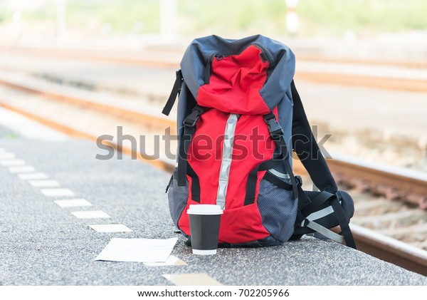 Backpack, map, cellphone and notebook on bench at train station. Travel concept