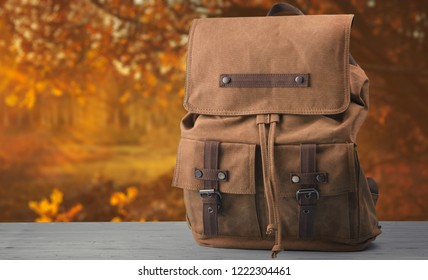 Backpack on the table on the autumn background