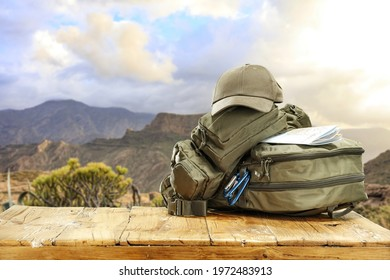 Backpack on wooden table and landscape of mountains. Summer tirp and free space for your decoration.