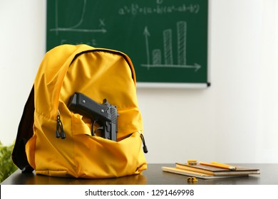 Backpack with pistol on table in classroom. No guns in school