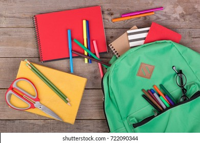 Backpack and school supplies: books, pencils, notepad, felt-tip pens, eyeglasses, scissors on brown wooden table