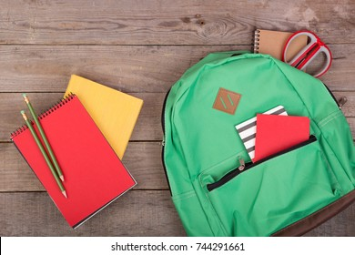 Backpack and school supplies: books, pencils, notepad, scissors on brown wooden table