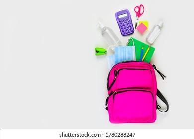 Rucksack mit Schulmaterial und COVID 19 Präventionsartikel. Draufsicht auf weißem Hintergrund. Zurück zur Schule während der Pandemie-Konzept.
