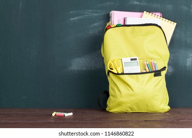 Backpack with school supplies front on the chalkboard