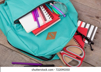 Backpack and school supplies: magnifying glass, notepad, felt-tip pens, eyeglasses, scissors on brown wooden table