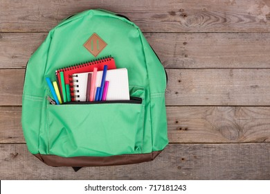 Backpack and school supplies: notepad, felt-tip pens on brown wooden table