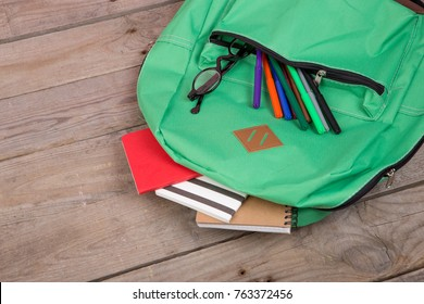 Backpack and school supplies: notepad, felt-tip pens, eyeglasses on brown wooden table