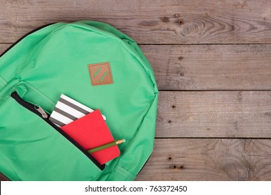 Backpack and school supplies: notepad, pencil on brown wooden table