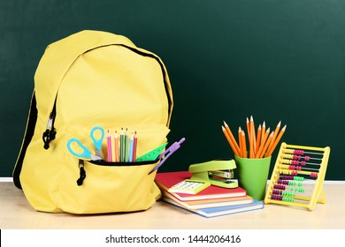 Backpack with school supplies on green background