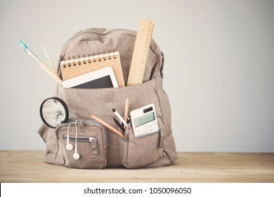 Backpack school supplies on table emtpy background