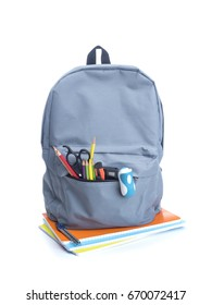 Backpack with school supplies on top of notebooks, isolated on white
