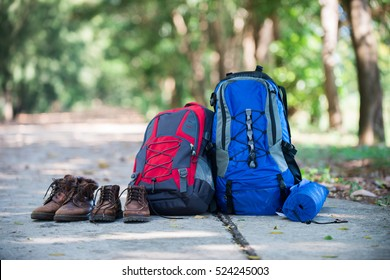 Backpack and shoes backpackers rest on the road while go hiking.