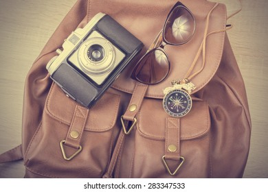 Backpack, sunglasses, necklace and old camera,  retouching Vintage