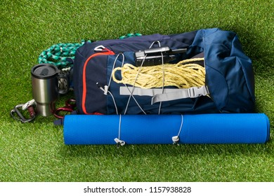 Backpack with things for sport and outdoor recreation lies on a green lawn